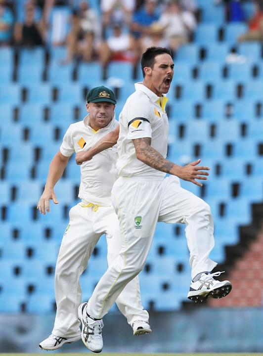 Australia's bowler Mitchell Johnson, right, with teammate David Warner, left, reacts after dismissing South Africa's batsman Faf du Plessis, for 3 runs on the second day of their their cricket
