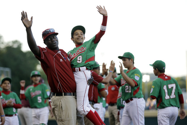Lugazi, Uganda manager Henry Odong, left, cheers with Nuevo Laredo, Mexico's Joel Turrubiates after a pool play baseball game at the Little League World Series, Saturday, Aug. 18, 2012, in South Willi