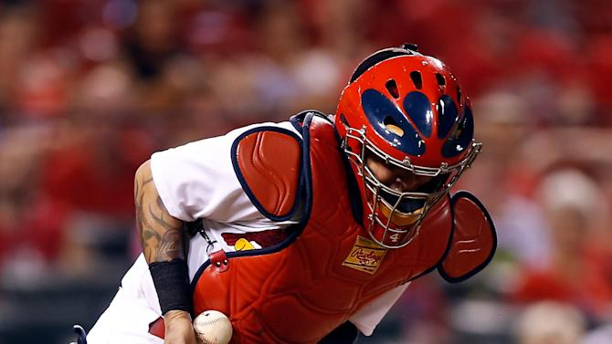 St. Louis Cardinals catcher Yadier Molina corrals the ball on an off throw during the ninth inning of a baseball game against the Cincinnati Reds Tuesday, July 28, 2015, in St. Louis. (AP Photo/Scott Kane)