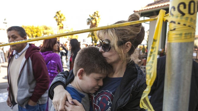 Parent Klara Esposito consoles her 10-year-old son, Tony, while waiting to meet with her 7-year-old son, Daniel, after their school was evacuated for a bomb threat in Glendale, Calif., Monday, Jan. 7, 2013. The bomb threat prompted the evacuation of hundreds of children from R.D. White Elementary School on Monday while police searched buildings to make sure the campus was safe. An anonymous caller phoned the school at around 8:30 a.m., and said there was a bomb at the campus, according to police Sgt. Tom Lorenz. (AP Photo/Damian Dovarganes)
