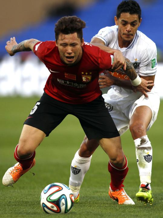 Josue of Brazil's Atletico Mineiro fights for the ball with Gao Lin of China's Guangzhou Evergrande during their 2013 FIFA Club World Cup third place soccer match in Marrakech stadium