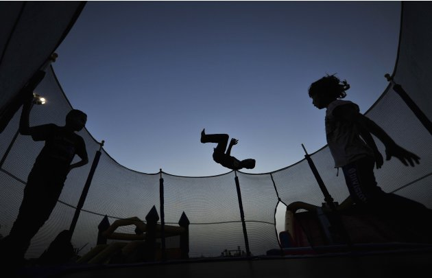Children play next to a jumping castle near the beach in Benghazi