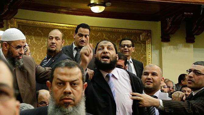 In this Monday, Feb. 27, 2012 photo, Egyptian lawmaker Anwar al-Balkimy, center, gestures during a session of parliament in Cairo, Egypt. Egypt's ultraconservative Islamic Al-Nour party said Monday one of its lawmakers has resigned from parliament because he got a nose job and then lied about it, claiming he was beaten. Lawmaker Anwar al-Balkimy told police he was attacked last week during an attempt to steal his car while he was driving on a highway on Cairo's outskirts. Then it turned out there was no carjacking, no beating and no robbery. Al-Balkimy just had a nose job. The problem with that is that his party follows a strict line of Islam that forbids cosmetic surgery as meddling in God's work. (AP Photo)
