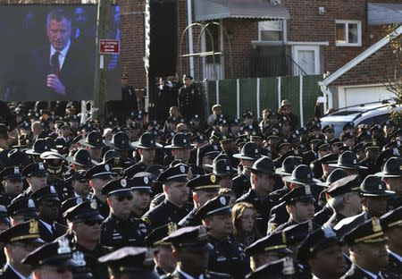 Law enforcement officers turn their backs on a video monitor as New York City Mayor de Blasio speaks during the funeral of slain NYPD officer Rafael Ramos near Christ Tabernacle Church in the Queens borough of New York