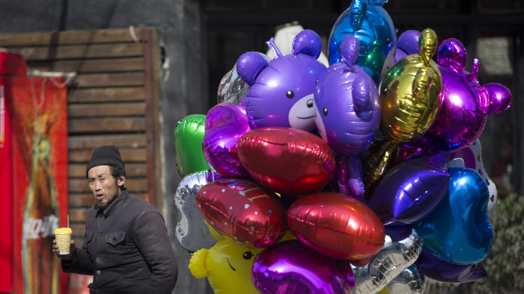 A chinese balloon vendor waiting for costumer in downtown Beijing, China, Friday, March 7, 2014. China today expressed confidence over achieving its GDP target of 7.5 per cent this year, citing the expected recovery of the world economy and strong fundamentals of emerging markets. (AP Photo/Vincent Thian)