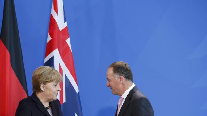 New Zealand's Prime Minister Key goes for a handshake with German Chancellor Merkel following their news conference at the Chancellery in Berlin
