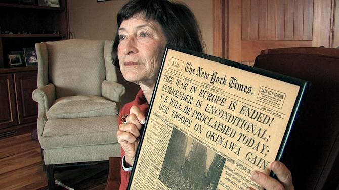 """In this Wednesday, May 2, 2012 image taken from video, Julia Kennedy Cochran, daughter of former AP Paris bureau chief Ed Kennedy, holds a copy of the New York Times published on May 8, 1945, at her home in Bend, Ore.  Kennedy was dismissed by The AP after he became the first journalist to file a firsthand account of German officials surrendering unconditionally to Allied commanders at a former schoolhouse in Reims, France. Sixty-seven years later, AP President and Chief Executive Officer Tom Curley said that Kennedy was right to stand up to the censors, and should have been commended, not fired. Cochran said she was """"overjoyed,"""" that the AP had taken an interest in exonerating him. """"I think it would have meant a lot to him,"""" she said. (AP Photo/Rick Bowmer)"""