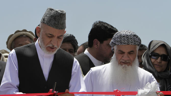 Afghan President Hamid Karzai, left, cuts ribbon with Afghanistan's Water and Power Minister Ismail Khan inaugurating the start of construction on a power plant in Shakardara district north of Kabul, Afghanistan, Tuesday, June 19, 2012. Shah wa Aroos power plant project in north of Kabul is one of the five development projects which is funded by Afghanistan's government, officials said. (AP Photo/Mohammad Ismail, Pool)