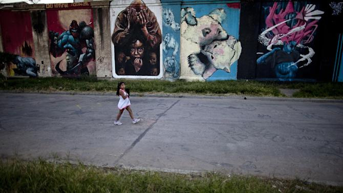 In this March 27, 2013 photo, a girl walks by a wall covered by four murals by artists, from left, Anita Messina and Emy Mariani; El Marian; Mati Quiroga; and Lucio Savant in the Barracas neighborhood of Buenos Aires, Argentina. The urban artists generally go door to door seeking approval from building owners before starting a mural. Owners usually agree, especially if the mural of aerosol, acrylic or oil paint will cover up political slogans and other graffiti already painted there. (AP Photo/Natacha Pisarenko)