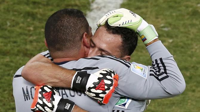 Colombia's goalkeeper Ospina hugs Mondragon as he is substituted by Mondragon during their 2014 World Cup Group C soccer match at the Pantanal arena in Cuiaba