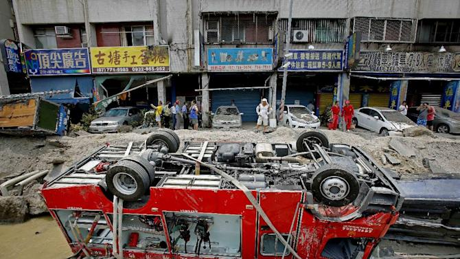A destroyed fire truck is seen overturned in the rubble after massive gas explosions in Kaohsiung, Taiwan, Friday, Aug. 1, 2014. A series of underground explosions about midnight Thursday and early Friday ripped through Taiwan's second-largest city, killing scores of people, Taiwan's National Fire Agency said Friday. (AP Photo/Wally Santana)