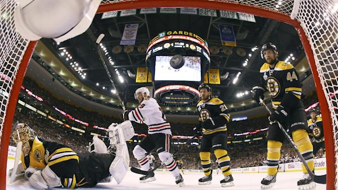 Boston Bruins goalie Tuukka Rask, left, of Finland, watches the puck caroms from the net on a shot by Chicago Blackhawks right wing Patrick Kane, not shown during the second period in Game 4 of the NHL hockey Stanley Cup Finals Wednesday, June 19, 2013, in Boston. Blackhawks center Jonathan Toews (19) celebrates as Bruins defensemen Andrew Ference (21) and Dennis Seidenberg (44), of Germany, watch. Chicago won 6-5 to even the series 2-2. (AP Photo/Harry How, Pool)
