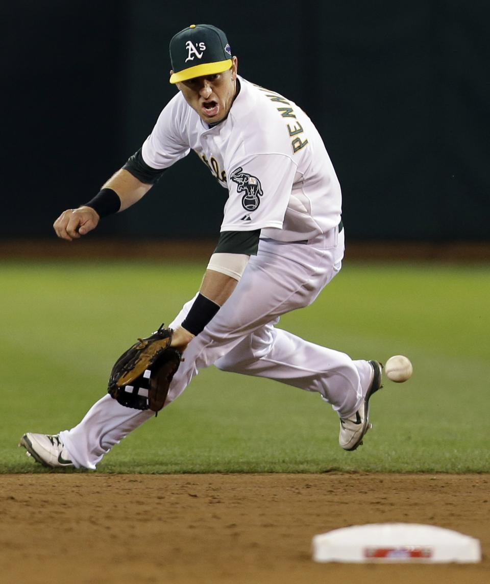 Oakland Athletics shortstop Cliff Pennington (2) chases down a ball hit by Detroit Tigers Andy Dirks in the second inning of Game 5 of an American League division baseball series in Oakland, Calif., Thursday, Oct. 11, 2012. Dirks was safe at first. (AP Photo/Marcio Jose Sanchez)
