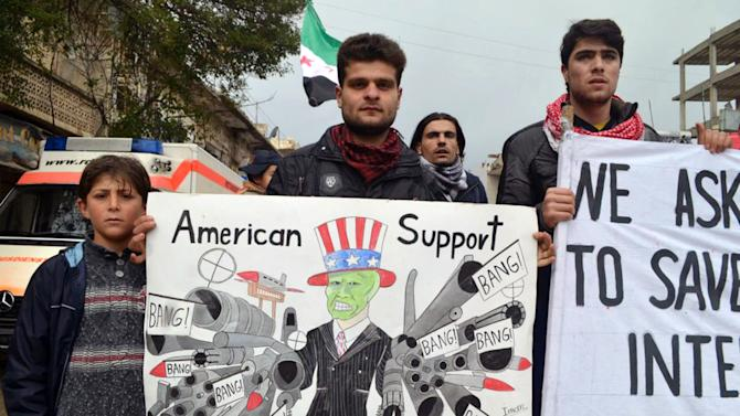 This citizen journalism image provided by Edlib News Network, ENN, which has been authenticated based on its contents and other AP reporting, shows anti-Syrian regime protesters holding a caricature placard during a demonstration, at Kafr Nabil town, in Idlib province, northern Syria, Friday, March. 1, 2013. Syrian government forces fought fierce clashes with rebels attacking a police academy near the northern city of Aleppo on Friday, while the bodies of 10 men most of them shot in the head were found dumped along the side of a road outside Damascus, activists said. (AP Photo/Edlib News Network ENN)
