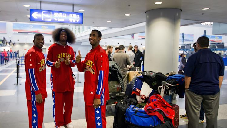 Members of the Harlem Globetrotters basketball team gesture as they prepare to check in with former NBA star Dennis Rodman, not in the photo, at the departure hall of Beijing Capital International Airport in Beijing Tuesday, Feb. 26, 2013. Dennis Rodman, and three members of the Harlem Globetrotters basketball team, a VICE correspondent and a production crew from the company are visiting North Korea to shoot footage for a new TV show set to air on HBO in early April, VICE told The Associated Press in an exclusive interview before the group's departure from Beijing. (AP Photo/Andy Wong)