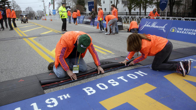 Race officials set up electronics at the starting line of the Boston Marathon, Monday, April 20, 2015, in Hopkinton, Mass. (AP Photo/Stephan Savoia)