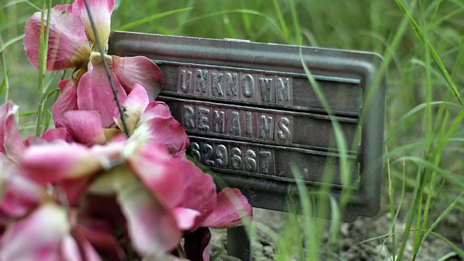 A small sign at a cemetery marks the grave site of an unidentified body found on a ranch, in Falfurrias, Texas, in this Aug. 23, 2013, photo. Brooks County, home to a Border Patrol checkpoint about an hour north of the border, handled 129 bodies last year of immigrants that died in their attempt to come to the U.S. Brooks County is now trying to improve its services by performing an autopsy on all immigrants and making greater efforts to identify them. (AP Photo/Eric Gay)