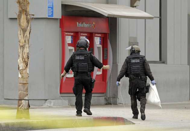 Los Angeles Police bomb squad members check for explosive devices outside a Bank of America branch in Los Angeles Wednesday, Sept. 5, 2012. Authorities say two gunmen kidnapped a bank manager, held her overnight and strapped a device to her stomach before robbing a Bank of America. The woman then had employees take money from the bank and put it outside. The suspects remain at large. (AP Photo/Damian Dovarganes)