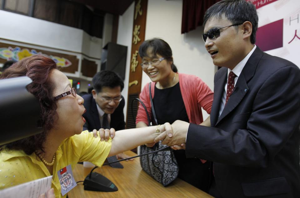 A supporter grabs a handshake from Chinese activist Chen Guangcheng and his wife Yuan Weijing after a keynote speech to lawmakers human rights supporters at the legislature in Taipei, Taiwan, Tuesday, June 25, 2013. Chen is on an 18-day tour of Taiwan meeting with human rights supporters and other key officials. (AP Photo/Wally Santana)