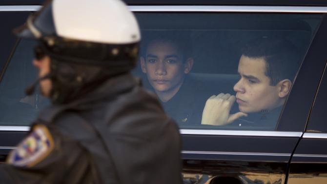 Justin and Jaden Ramos sit in a limo and watch motorcycle officers ride past after the casket of their father, slain NYPD officer Rafael Ramos was loaded into a hearse at his funeral in New York