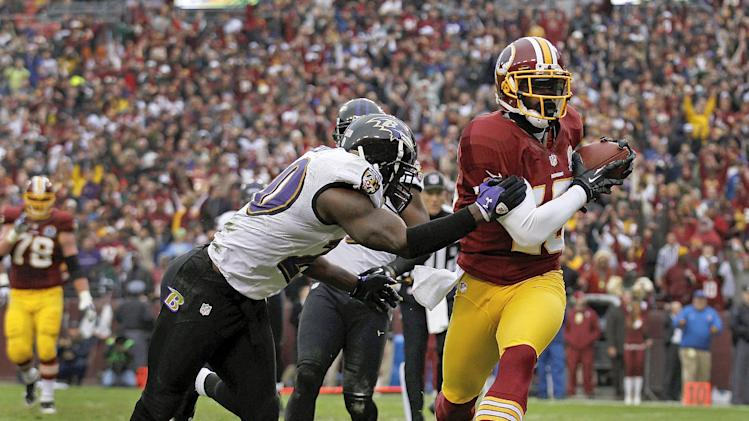 Washington Redskins wide receiver Josh Morgan carries the ball into the end zone for a touchdown as Baltimore Ravens free safety Ed Reed tries to stop him during the first half of an NFL football game in Landover, Md., Sunday, Dec. 9, 2012. (AP Photo/Alex Brandon)