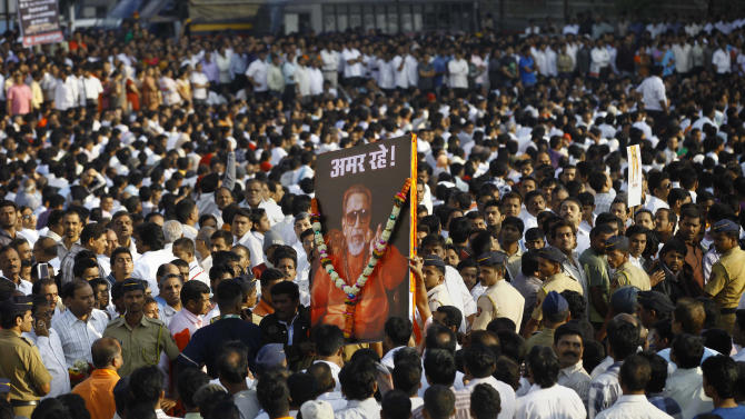 """Indian mourners carry a poster of Hindu hardline Shiv Sena party leader Bal Thackeray with the words """"Long Live"""" during his funeral in Mumbai, India, Sunday, Nov. 18, 2012. Thackeray, the extremist leader linked to waves of mob violence against Muslims and migrant workers in India, died Saturday after an illness of several weeks. He was 86. (AP Photo/Rafiq Maqbool)"""