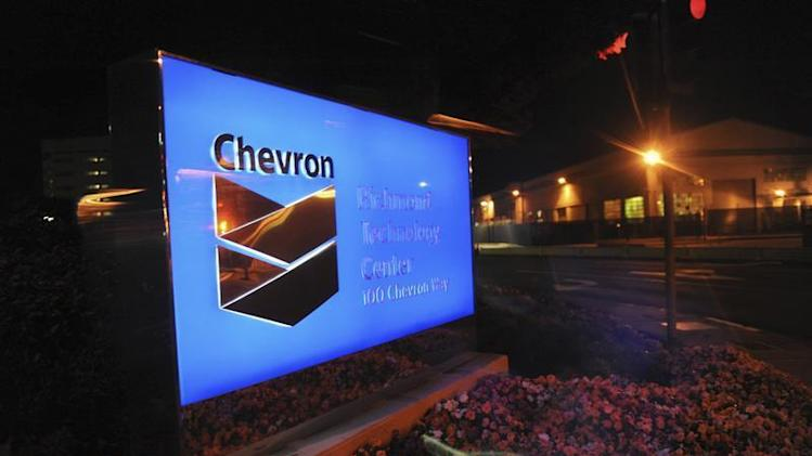 A lit sign at Chevron's oil refinery in Richmond, California is seen through a window after a large fire erupted earlier in the evening