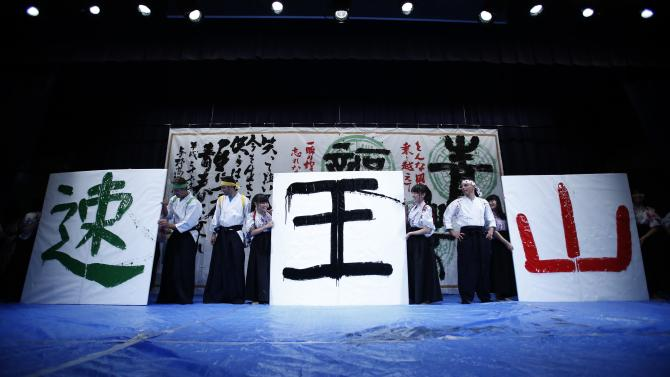 "Nibali of Italy and Majka of Poland look at a calligraphy of a Chinese character ""Speed"", written by Sagan of Slovakia, as they write Chinese characters of each title during a calligraphy performance, an exchange event with local students in Saitama"