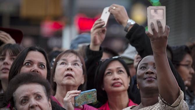 People hold up their mobile devices as they stand in front of a billboard owned by Revlon in New York
