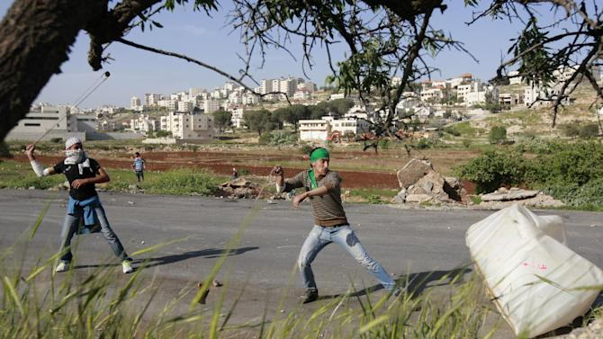 A Palestinian youths use slingshots to hurl stones towards Israeli solders during clashes outside Ofer, an Israeli military prison near the West Bank city of Ramallah, Wednesday, April  3, 2013. Protests broke after a Palestinian prisoner Maysara Abu Hamdiyeh died of cancer in an Israeli jail. (AP Photo/Majdi Mohammed)