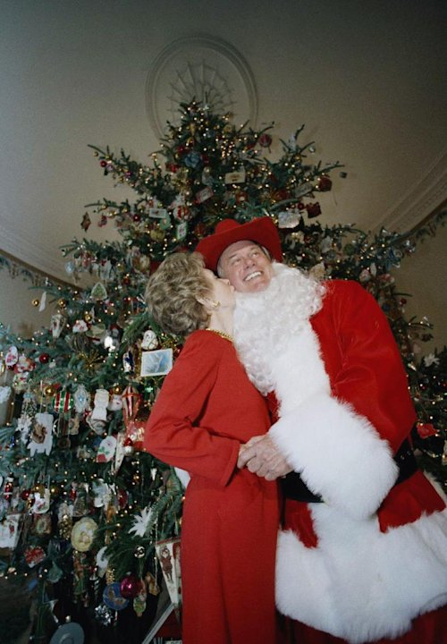 FILE - In this Monday, Dec. 9, 1985 file photo, first lady Nancy Reagan kisses actor Larry Hagman, playing Santa Claus, at a showing of the holiday decorations at the White House in Washington.  Actor