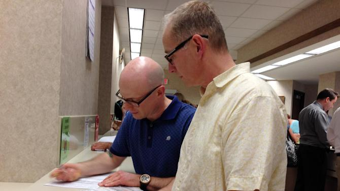 Mark Williams, left, and Chrisopher Martell, right, fill out an application for a marriage license at the Milwaukee County Clerk's office Friday, June 6, 2014, in Milwaukee. Same-sex couples began getting married in Wisconsin on Friday shortly after a federal judge struck down the state's gay marriage ban and despite confusion over the effect of the ruling. (AP Photo/M.L.Johnson)