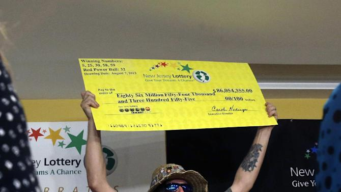 """Lottery winner William L. Seeley shouts as he holds up a sign made as a check Tuesday, Aug. 13, 2013, in Toms River, N.J. The """"Ocean's 16,"""" as a group of 16 public employees on the Jersey shore has been dubbed after snagging one of three winning tickets in last week's $448 million Powerball jackpot, gathered at an afternoon news conference in Toms River, where they work for the Vehicle Services department. The event comes one day after the nine women and seven men claimed their share of the jackpot. (AP Photo/Mel Evans)"""