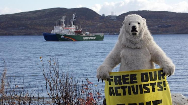 A Greenpeace activist dressed as a polar bear holds a banner in front of the Arctic Sunrise protest ship in Kola Bay, Murmansk, on September 24, 2013