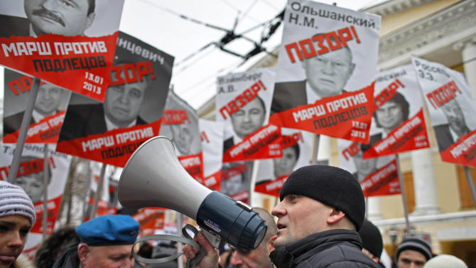 "Opposition leader Sergei Udaltsov, foreground, speaks during a protest rally in Moscow, Russia, Sunday, Jan. 13, 2013. Thousands of people are gathering in central Moscow for a protest against Russia's new law banning Americans from adopting Russian children. They carry posters of President Vladimir Putin and members of Russia's parliament who overwhelmingly voted for the law last month. The posters have the word ""Shame"" written in red over the faces and proclaim that Sunday's demonstration is a ""March Against the Scum"" who enacted the law.(AP Photo/Alexander Zemlianichenko)"
