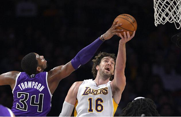Los Angeles Lakers center Pau Gasol, right, of Spain, puts up a shot as Sacramento Kings forward Jason Thompson defends during the second half of an NBA basketball game Sunday, Nov. 24, 2013, in Los A