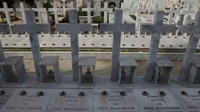 "Graves of persons killed during the 1974 Turkish invasion of Cyprus, while the words in Greek read ""unknown soldier"" fell in battle against the Turks"", at Lakatamia military cemetery in the Cypriot capital Nicosia, Thursday, Nov. 29, 2012. A Cyprus court has ordered the government to pay  Euro 324,000  ($419,668 approx) in damages to the wife and two daughters of a soldier who was killed during Turkey's 1974 invasion of the country but who was listed as missing in action for more than two decades.  (AP Photo/Petros Karadjias)"