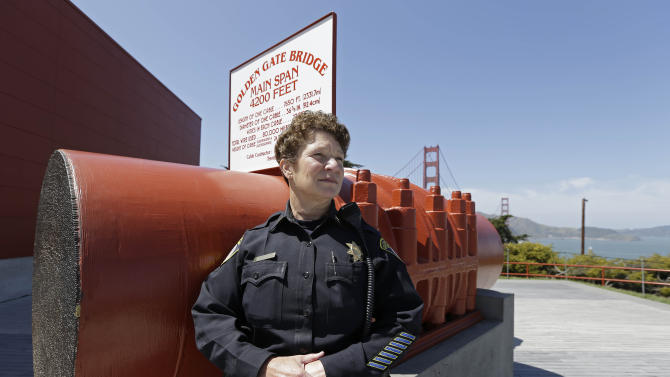In the photo taken Tuesday, April 30, 2013 Golden Gate Bridge Capt. Lisa Locati poses by a section of the bridge at its visitors center in San Francisco. About 1,500 people have plunged from the bridge, making it one of the world's favorite suicide spots. (AP Photo/Eric Risberg)