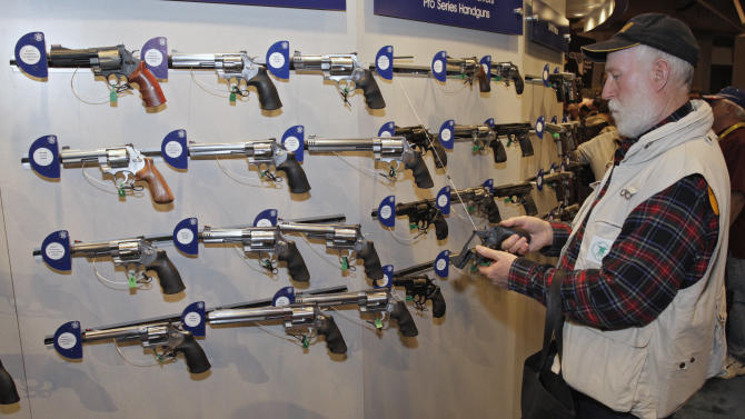 Van Meter, of Rhineland, WI, inspects a revolver during the National Rifle Association's (NRA) 141st Annual Meetings & Exhibits in St. Louis