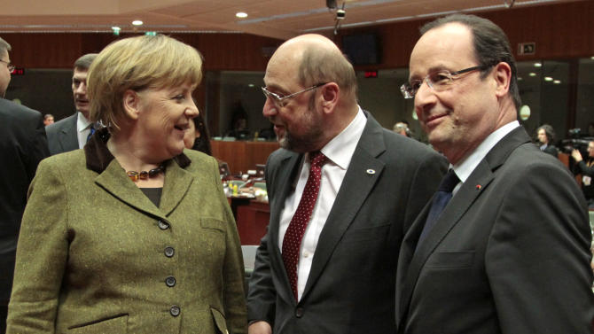 German Chancellor Angela Merkel, left, talks with European Parliament President Martin Schulz, center, and French President Francois Hollande, during the EU Budget summit at the European Council building in Brussels, Thursday, Feb. 7, 2013. European Union leaders drew hard lines Thursday ahead of a struggle over EU spending for the next seven years that reflects deep divisions about the role of their union. (AP Photo/Yves Logghe)
