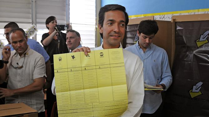 """In this image released by the New Progressive Party, Puerto Rico's Gov. Luis Fortuno shows his ballot to the press as he votes at a polling station in Guaynabo, Puerto Rico, Tuesday, Nov. 6, 2012. Puerto Ricans are electing a governor as the U.S. island territory does not get a vote in the U.S. presidential election. But they are also casting ballots in a referendum that asks voters if they want to change the relationship to the United States. A second question gives voters three alternatives: become the 51st U.S. state, independence, or """"sovereign free association,"""" a designation that would give more autonomy. (AP Photo/New Progressive Party, Jerry Guillen)"""