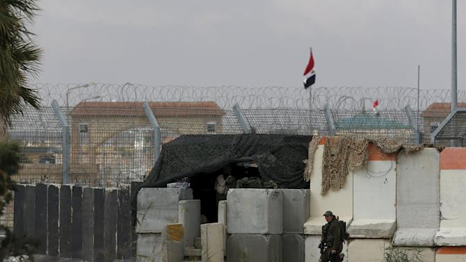 An Israeli soldier stands next to concrete barriers near Israel's border fence with Egypt's Sinai peninsula, in Israel's Negev Desert