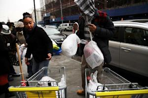 A volunteer hands out free turkeys at CAMBA's Beyond…