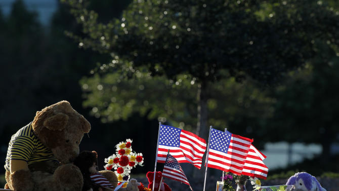 """The sun rises between flags placed at a memorial near the the Century 16 movie theater Sunday, July 22, 2012, in Aurora, Colo. Twelve people were killed and dozens were injured in a shooting attack early Friday at the packed theater during a showing of the Batman movie, """"The Dark Knight Rises."""" Police have identified the suspected shooter as James Holmes, 24. (AP Photo/Alex Brandon)"""