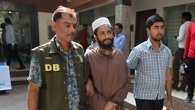 Police officers in Dhaka detain Abdul Haque on suspicion he was involved in Islamic State propaganda
