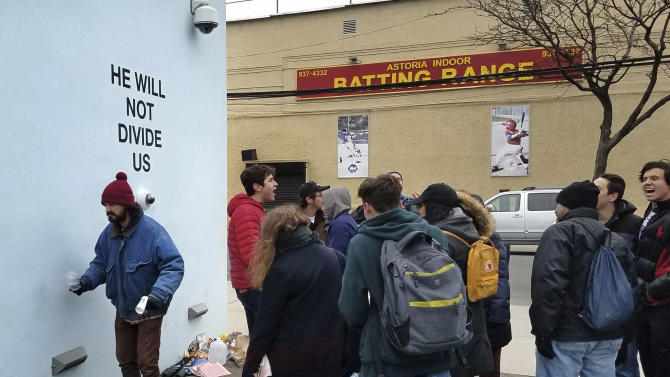 """Actor Shia LeBeouf, left, stands in front of a live-steam camera with the words """"HE WILL NOT DIVIDE US"""" posted on a wall outside of the the Museum of the Moving Image as members of the public join LeBeouf in chanting the words """"He will Not Divide Us"""" in the Queens borough of New York. LaBeouf has spent the first four days of the Trump presidency swaying, dancing and chanting, along with anyone who wants to join in. The project by LeBeouf and two other artists opened on Jan. 20 and is expected to go for 4 years, or for """"the duration of the presidency."""" (AP Photo/Deepti Hajela)"""
