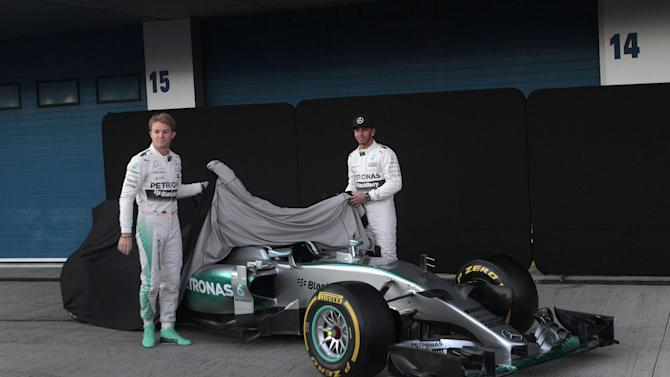 Mercedes Formula One racing driver Lewis Hamilton, right, of Britain, and teammate Nico Rosberg of Germany unveil a new Mercedes F1 M06 car at the Circuito de Jerez on Sunday, Feb. 1, 2015, in Jerez de la Frontera, Spain. (AP Photo/Miguel Morenatti)