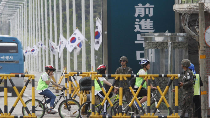 South Korean students riding bicycles pass by army soldiers on Unification Bridge in Paju, South Korea, near the border village of Panmunjom, Sunday, May 19, 2013. The South Korean military on Sunday have beefed up monitoring on North Korea and are maintaining a high-level of readiness to deal with any risky developments to guard against possibilities of additional missile launches and other types of provocations. (AP Photo/Ahn Young-joon)