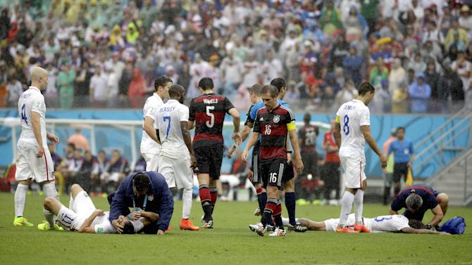 United States' Alejandro Bedoya, left, and United States' Jermaine Jones lie on the pitch after colliding during the group G World Cup soccer match between the USA and Germany at the Arena Pernambuco in Recife, Brazil, Thursday, June 26, 2014