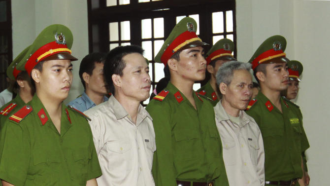 Doan Van Vuon, second from left and his brother Doan Van Sinh, fourth from left, stand trial at the court in the northern city of Haiphong, Vietnam on Tuesday April 2, 2013. The two along with their two other relatives were charged with attempted murder when they attacked authorities who came to evict their fish farm injuring seven police and army officers in the incident last year. (AP Photo/Vietnam News Agency, Bui Doan Tan)